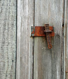 Latch and Lock. An ornate but weathered and rusted latch and pin on a aged wooden shed Stock Photo