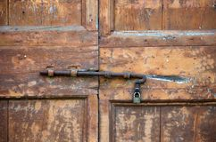 Latch of an old door. Rusty latch with padlock of an old wooden door stock image