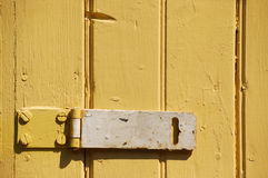 Latch on Yellow Siding. Metal latch screwed onto wooden yellow siding Stock Photography