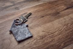 Latchkey with key chain. Home key attached to a key chain in shape of a house. Lying on a dark brown surface with wooden texture Royalty Free Stock Photography