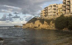 Late afternoon in Autumn beside harbour at Marsalforn on Gozo, Malta. Cloudy skies in late afternoon in Autumn beside harbour at Marsalforn on Gozo, Malta Stock Photo