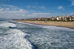 Late afternoon cityscape view of Manhattan Beach California, as seen from the pier, as waves from the Pacific Ocean roll in.  royalty free stock photos