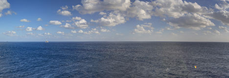 Late afternoon HDR panorama photo of sea spanning all the way to the horizon and blue cloudy sky.  stock image