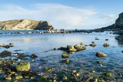 Late afternoon at Lulworth Cove, Dorset. Lulworth Cove, Dorset, showing the foreshore and cove in late afternoon sun Royalty Free Stock Image
