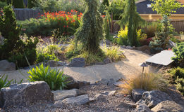 Late Afternoon Path. A curved path winds through this backyard perennial garden in the late afternoon sun Stock Photo