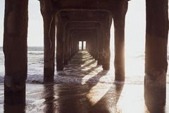 Late afternoon sun underneath the Manhattan Beach Pier along the Pacific Ocean coastline in Southern California.  royalty free stock image
