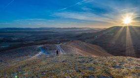 Late afternoon walk in the Pentlands. Sunset in the Pentlands, with a lone hiker some way off in the distance and the Lammermuir Hills in the background. Crisp Stock Photography