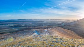 Late afternoon walk in the Pentlands. Sunset in the Pentlands, with a lone hiker some way off in the distance and the Lammermuir Hills in the background. Crisp Royalty Free Stock Photos