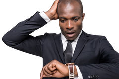 Late again!. Worried young African man in formalwear checking time while looking at his watch and standing isolated on white background Royalty Free Stock Images