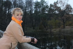 Late autumn in the forest, forest lake, blonde coat girl by the lake Stock Images