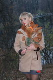 Late autumn in the forest, forest lake, blonde coat girl by the lake Stock Photo