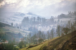 Late autumn misty morning in a village. First Snow Stock Images