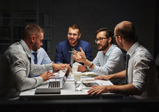 Late briefing. Intercultural businessmen discussing situation on stock market at briefing Royalty Free Stock Photography