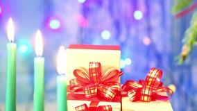 Late Christmas candles and gifts with red bows on a blue background with herlands in the side. Camera moves to dolly from left to right stock footage