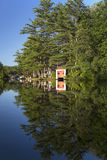 Late day on the river. Boat house and various buildings and boats on a river in New Hampshire in late day sun, entire scene reflected in still water Stock Photo