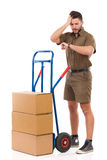 Late with a delivery. Delivery man standing close to a push cart, checking time at wristwatch and holding hand on head. Full length studio shot isolated on white Royalty Free Stock Images