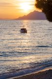 Sunset motorboat on the Adriatic sea beach in Makarska, Croatia. Late evening beach life landscape with sunset sunbeams above the mountains on the background stock images
