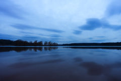 Late evening blue land and sky reflected like a mirror in calm l Stock Photography