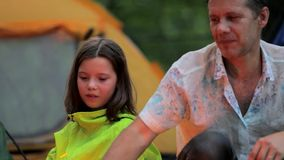 Late evening in camp, father and daughter sitting stock video footage