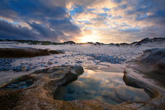 Late evening landscape beach over rocky shore and glowing sunset Stock Photography