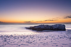 Late evening landscape of ocean over rocky shore with clouds blo Stock Photos