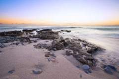 Late evening landscape of ocean over rocky shore with clouds blo Royalty Free Stock Photos
