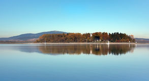 Late evening at Slanica Island, Oravska Priehrada. Late autumnal evening view of Slanica Island (Slanicky ostrov) and deep waters of Orava reservoir (Oravska stock photography