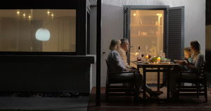 Late family dinner in outdoor terrace. Mother, son and grandparents having dinner in outdoor terrace by the house, lit candles on the table. child playing with stock video