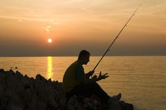 Late fishing. Shaadow fisherman Stock Photo
