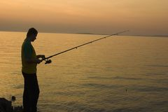 Late fishing. Shadow fisherman Stock Image