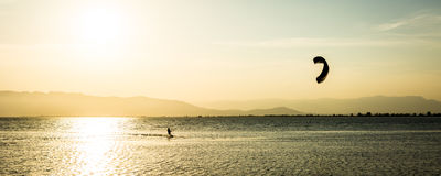 Late kitesurfing. A person doing kitesurf in a calmed bay at sunset Stock Photography