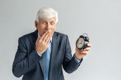 Late for Meeting. Businessman standing isolated on gray with alarm clock covering mouth surprised royalty free stock photo
