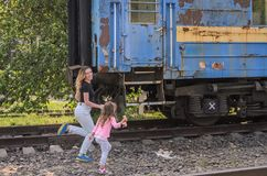 Late mom and daughter catch up with the departing train running after the old railway carriage.  Royalty Free Stock Images