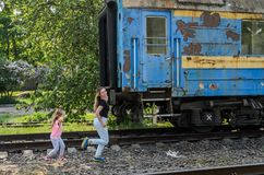 Late mom and daughter catch up with the departing train running after the old railway carriage.  Stock Photo