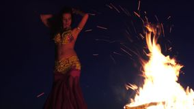 Late night a girl in the sand dancing belly dancing near a bright campfire stock video footage