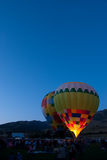 Late night Glow. Glowing hot air balloon grounded around crowd in evening light Stock Photography