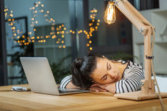 Hard working tired woman sleeping at work. Late at night. Hard working beautiful tired woman sitting in front of her laptop and sleeping while working late at Stock Photo