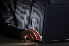 Late night internet addiction or working late. Man using laptop at a desk in the dark Royalty Free Stock Image