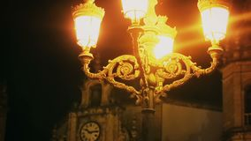Late night in old medieval city, street lamp lighting ancient clock, history. Stock footage stock video footage