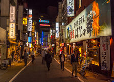 Late night scene of people walking on a shopping street in Shinjuku Tokyo. People stroling in a nighttime scene in Shinjuku street in Tokyo Royalty Free Stock Image