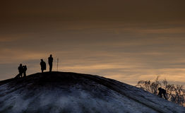 Late night sledders. A snow-covered hill with late-night sledders silhouetted against a sunset stock photos