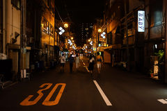 Late Night Street View in Osaka. Osaka, Japan - August 05, 2014 : Late Night Street view, people are walking in the middle of the road towards the incoming car Stock Image
