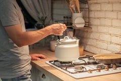 Late night tea habit man putting kettle stove. Late night tea habit. Cropped shot of man putting old style kettle on stove. Modern kitchen background royalty free stock image