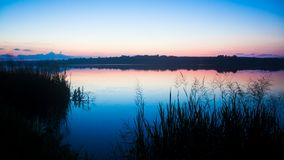 Late, quiet and peaceful summer evening on a large countryside pond. Late, quiet colourful, cloudless and peaceful summer evening on a large countryside pond stock photos