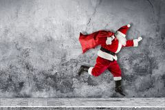 Late Santa claus in a hurry with traditional red white costume a royalty free stock photos