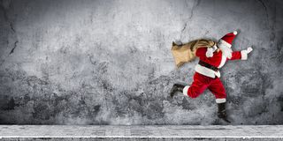 Late Santa claus in a hurry with traditional red white costume a stock images