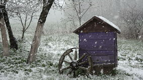 Late spring snowfall in garden on beehive and wheel, slow motion stock video