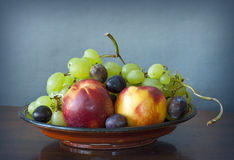 Late summer fruit assortment. Tray with fresh fruits; plums, grapes, peaches Stock Photos