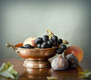 Late summer fruits in a copper bowl. Still life, summer fruits in an ancient copper bowl: figs, peaches, grapes with leaves on a wooden table Royalty Free Stock Photos