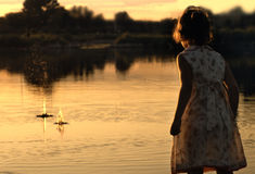 Late Summer Pond. Little girl skipping rocks on pond at sunset Royalty Free Stock Photos